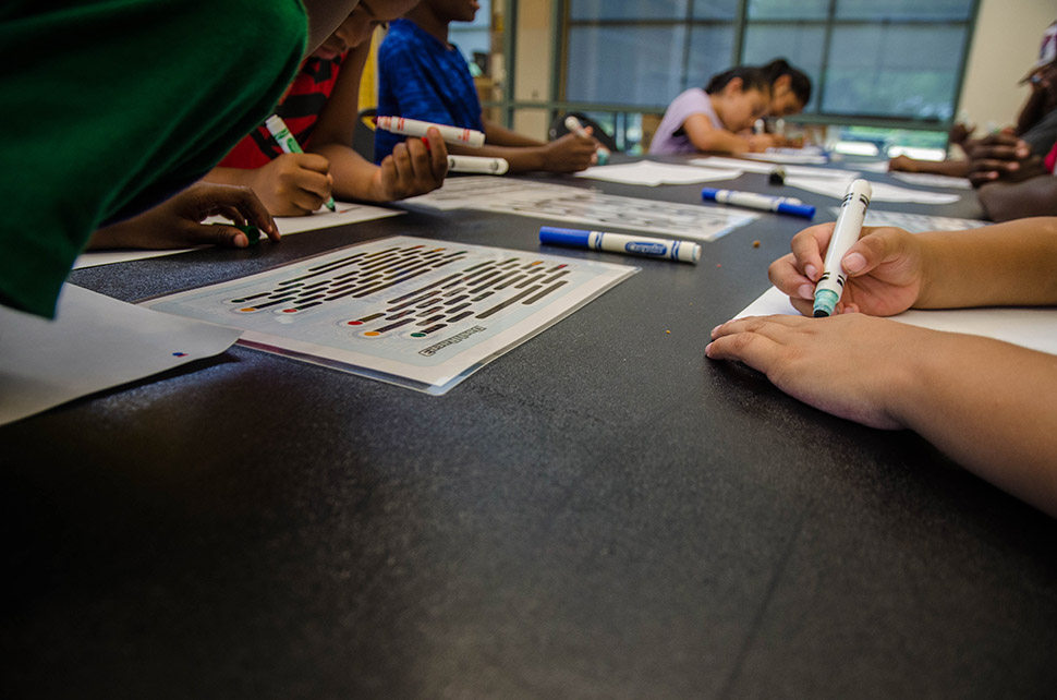 Children color patterns on pieces of paper at during a Perot Tech Truck science lesson. [ Photo by Hannah Ridings ]