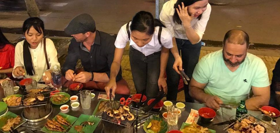 EMBA and GLEMBA students at a street food vendor being shown how to grill their dinner.