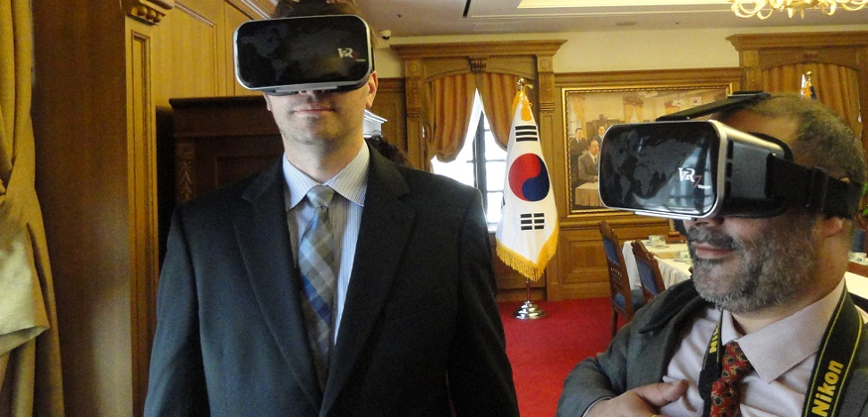 "Executive MBA students Dustin West (left) and Ramneek Bali, with Ericsson, use virtual reality goggles in a banquet room at the Bank of Korea to ""watch an event"" held years ago in the same room."